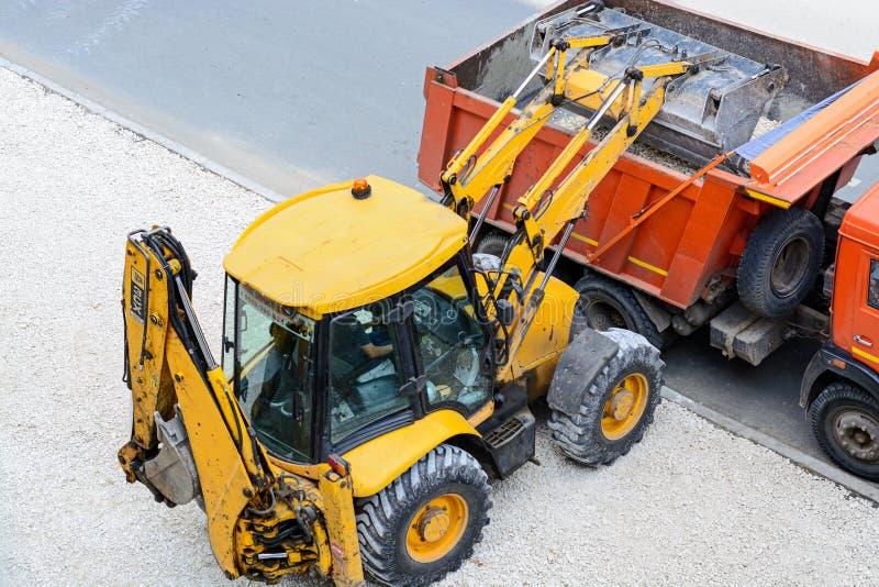 拖拉机装货石渣到卡车里 建筑垄沟安装道路工程 免版税库存照片