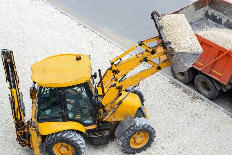 拖拉机装货石渣到卡车里 建筑垄沟安装道路工程 库存照片