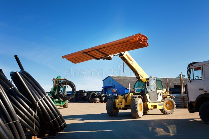 拖拉机装载堆黑pvc塑料管子户外仓库外 库存照片
