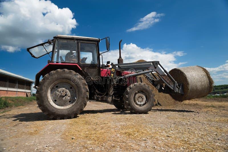 拖拉机运载的干草捆在堆滚动-堆积他们 收集大包在领域的干草的农业机器 免版税库存图片
