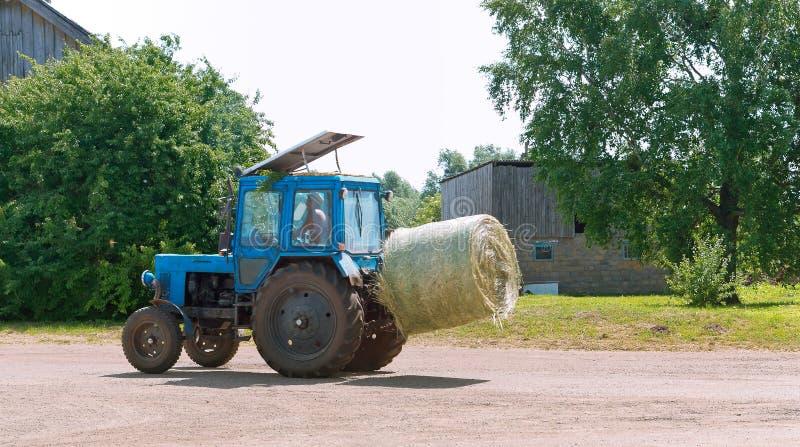 拖拉机运输扭转的捆干草,在农业机器的拖车的秸杆卷 图库摄影