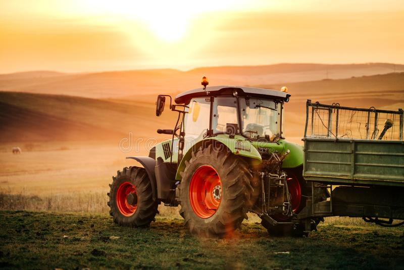 拖拉机,工作在与拖拉机的领域的农夫细节在日落背景 农业产业细节 图库摄影