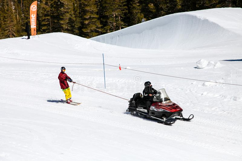 拖曳一个滑雪者的雪机动性在高山脉美国6月和马默斯Mountain,加利福尼亚冬季体育麦加  免版税库存照片