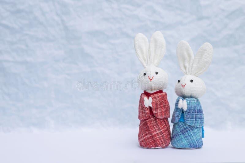拖曳在日本蓝色和红色礼服的小的兔子玩偶在被弄脏的背景 免版税库存图片