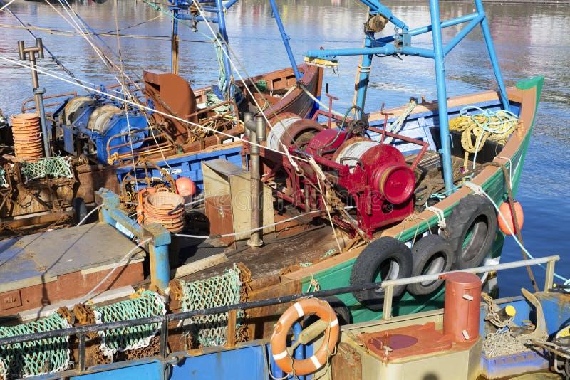 拖网渔船渔船明亮的颜色由阳光点燃了在港口口岸船坞在沿海 库存照片
