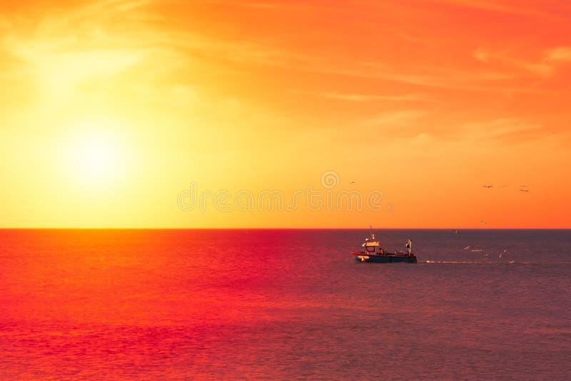 拖网渔船返回端起在日落 图库摄影
