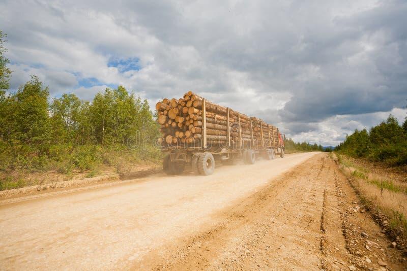 拖车被装载的森林在乡下公路去 免版税库存照片