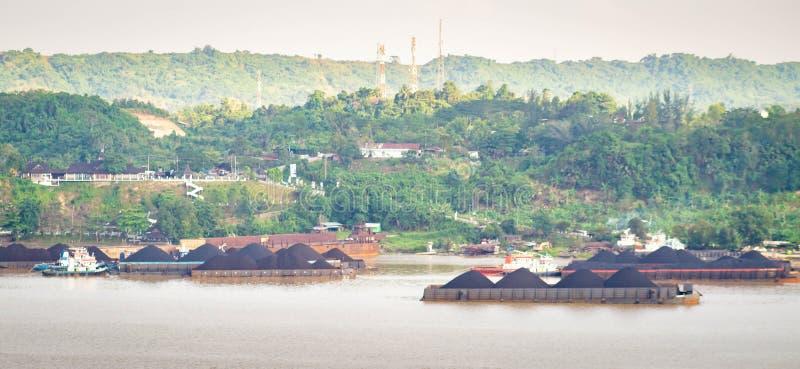 拖轮交通看法拉扯煤炭的驳船在马哈坎河,沙马林达,印度尼西亚 免版税库存照片
