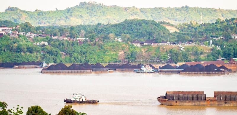 拖轮交通看法拉扯煤炭的驳船在马哈坎河,沙马林达,印度尼西亚 免版税图库摄影