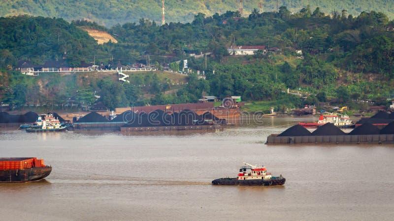 拖轮交通看法拉扯煤炭的驳船在马哈坎河,沙马林达,印度尼西亚 免版税库存图片