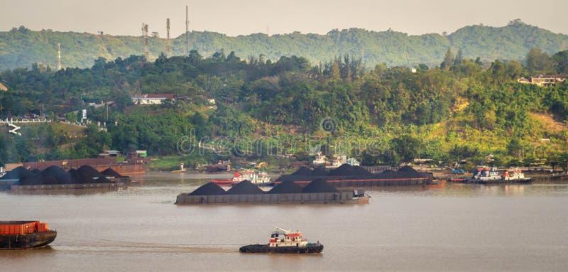 拖轮交通看法拉扯煤炭的驳船在马哈坎河,沙马林达,印度尼西亚 库存图片
