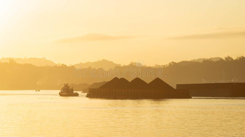拖轮交通美丽的景色拉扯煤炭的驳船在马哈坎河,沙马林达,印度尼西亚在黎明 库存图片