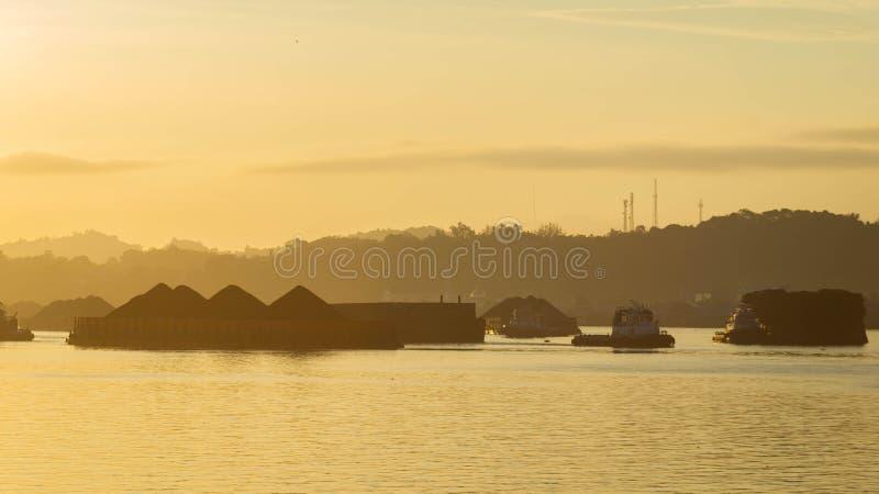 拖轮交通美丽的景色拉扯煤炭的驳船在马哈坎河,沙马林达,印度尼西亚在黎明 图库摄影