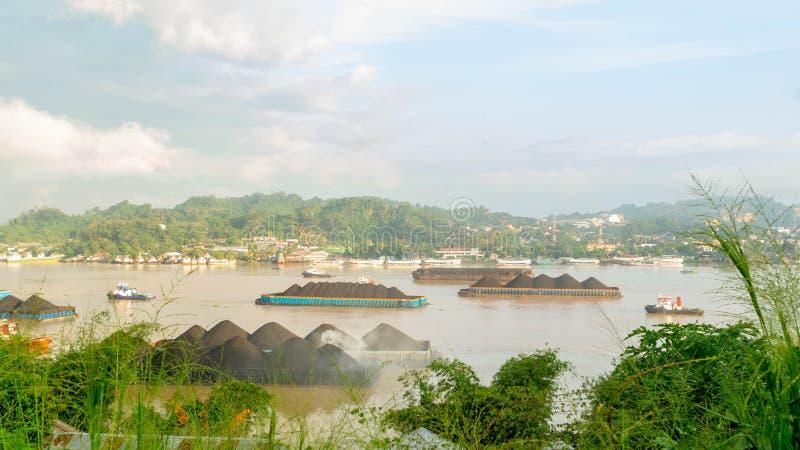 拖轮交通美丽的景色拉扯煤炭的驳船在马哈坎河,沙马林达,印度尼西亚 免版税库存照片