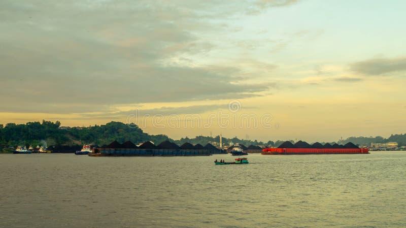 拖轮扯拽的驳船交通充分在马哈坎河,沙马林达,印度尼西亚的煤炭 免版税库存照片