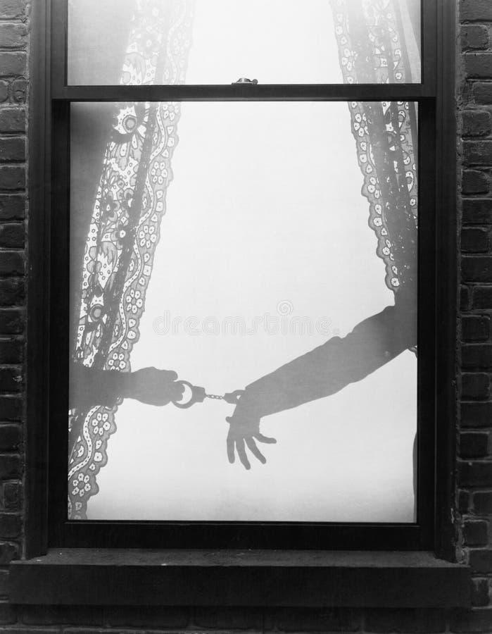拘捕有手铐的手的剪影一个人被观看通过窗口(所有人被描述不是更长生存和不 免版税库存图片