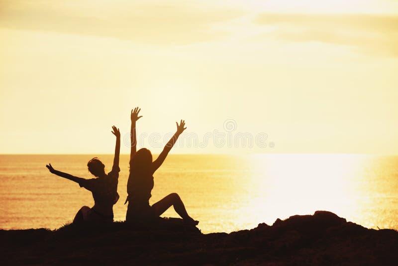 招呼两个愉快的女孩日落海 图库摄影