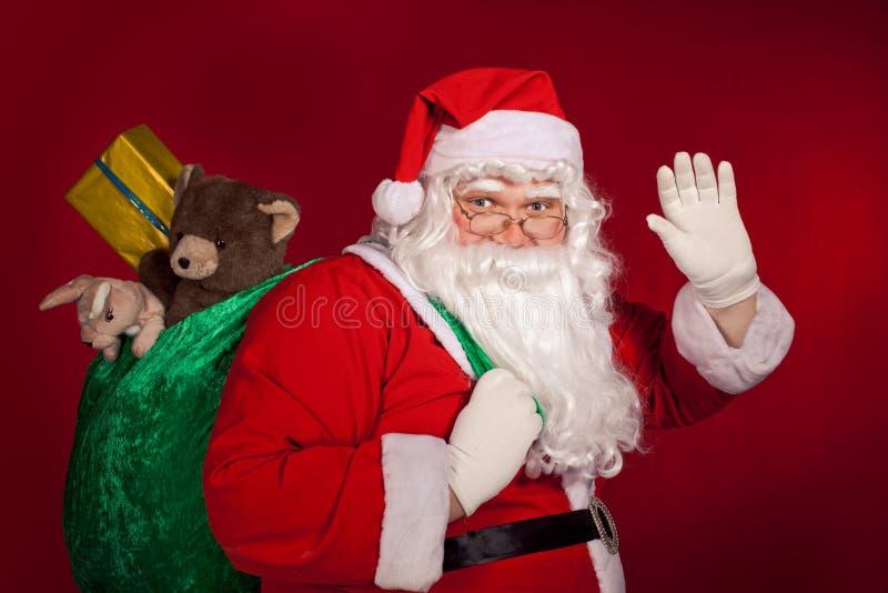招呼和拿着他的袋子的圣诞老人 免版税库存照片