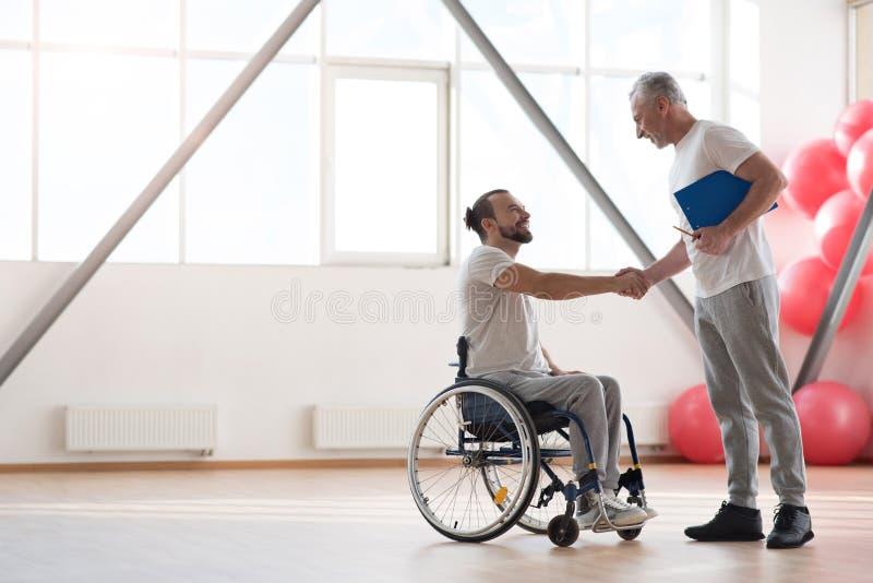 招呼快乐的残疾的患者他的健身房的理疗师 库存图片