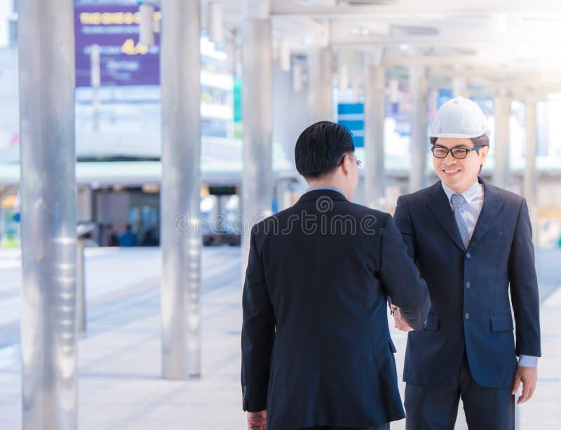 招呼男性的建筑师画象有安全安全帽的他的伙伴 显示握手的年轻人建造者 概念另外现有量合伙企业编结难题二 小组 库存照片