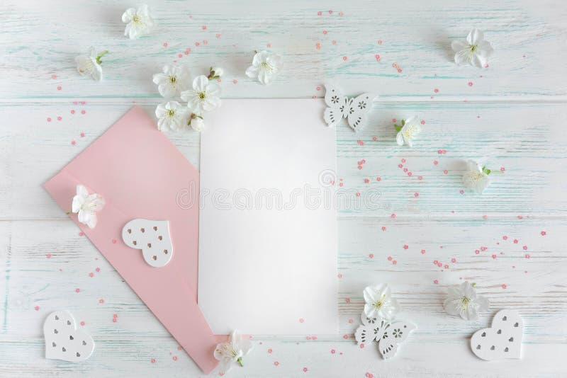 招呼的题字的假装信件 在轻的木背景的一封信件与一个桃红色信封和春天花  免版税库存照片