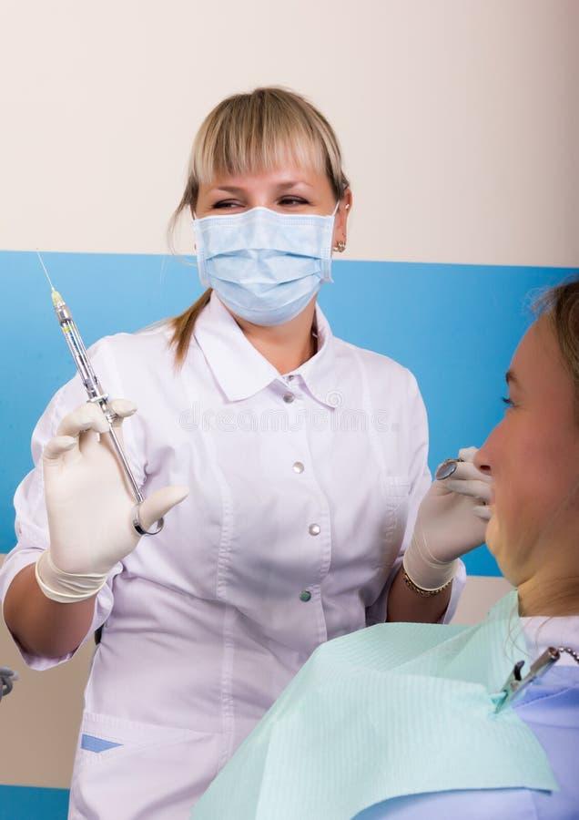 招待会是在医生审查在蛀牙的口腔的女性牙医 免版税库存图片