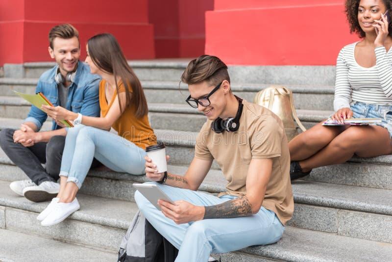 招待在台阶的快乐的毕业生临近大学大厦 免版税库存照片