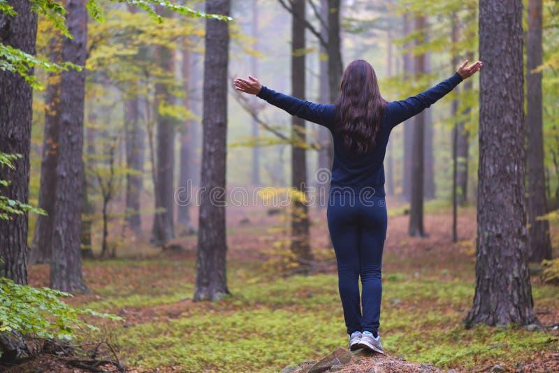 崇拜与开放胳膊的妇女在有黄色,绿色和红色叶子的秋天有薄雾的森林里 免版税库存图片