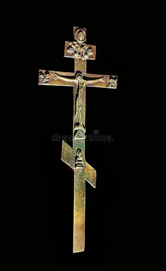 拜占庭式的古铜色十字架特写镜头与发光对此的太阳的在黑色隔绝了 免版税库存照片