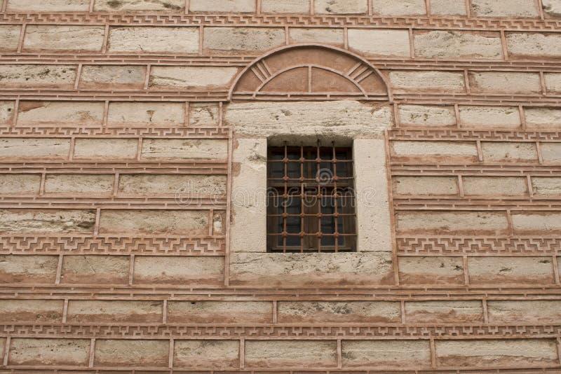 拜占庭式的砖砌、一个老大厦的墙壁与窗口的和伪造的金属格子 库存图片