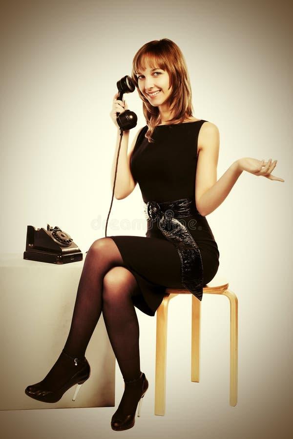 拜访减速火箭的电话的愉快的年轻时尚妇女 免版税库存图片