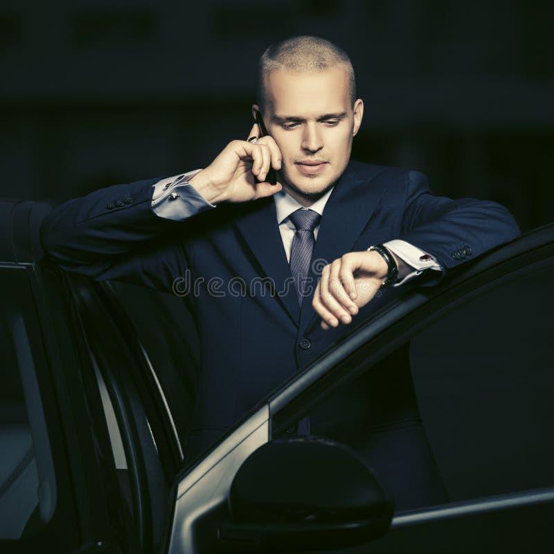 拜访在一辆他的汽车之外的年轻商人手机 库存照片