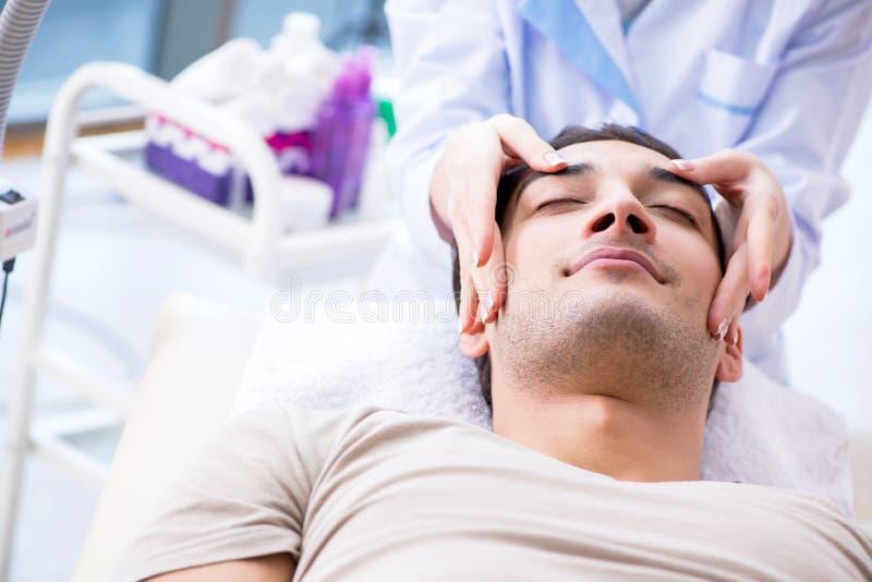 拜访女性医生美容师的年轻帅哥 免版税图库摄影