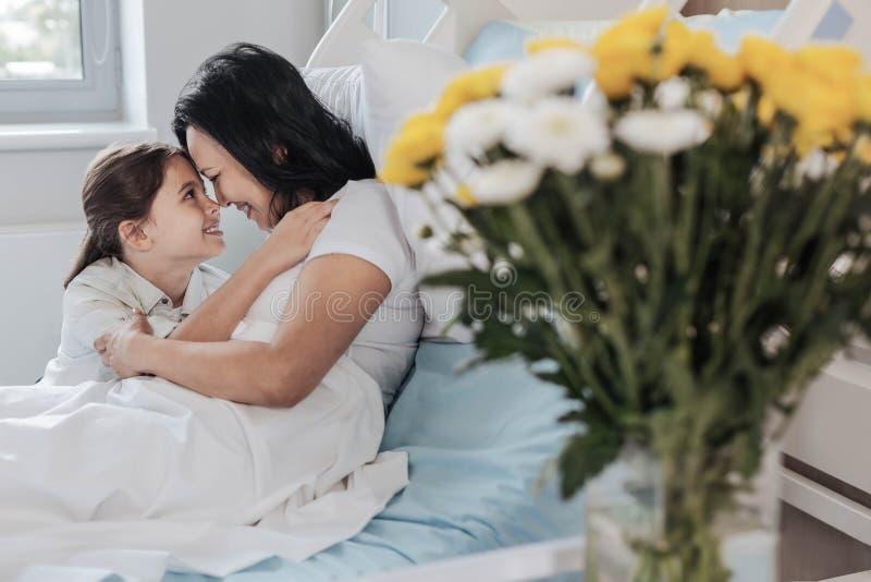 拜访她不适的母亲的爱恋的女儿在医院 库存图片