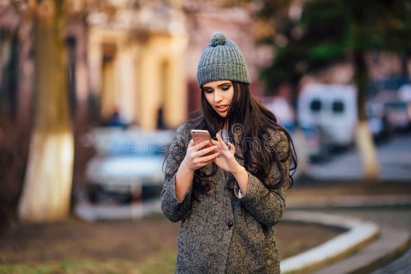拜访她的在春天城市街道上的年轻美丽的偶然女孩手机 库存照片