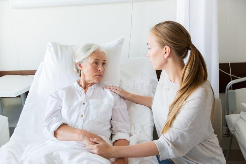 拜访她的资深母亲的女儿在医院 库存照片