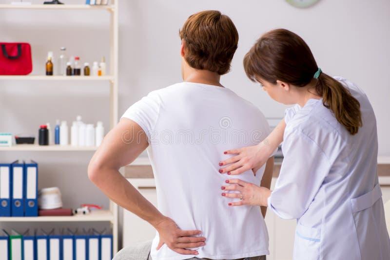 拜访年轻女性医生按摩医生的男性患者 图库摄影