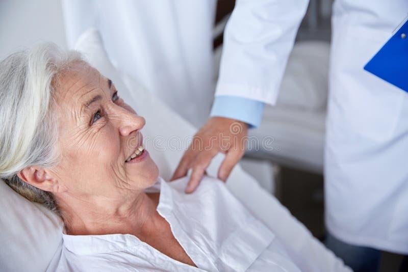 拜访愉快的资深妇女的医生在医院 免版税库存图片