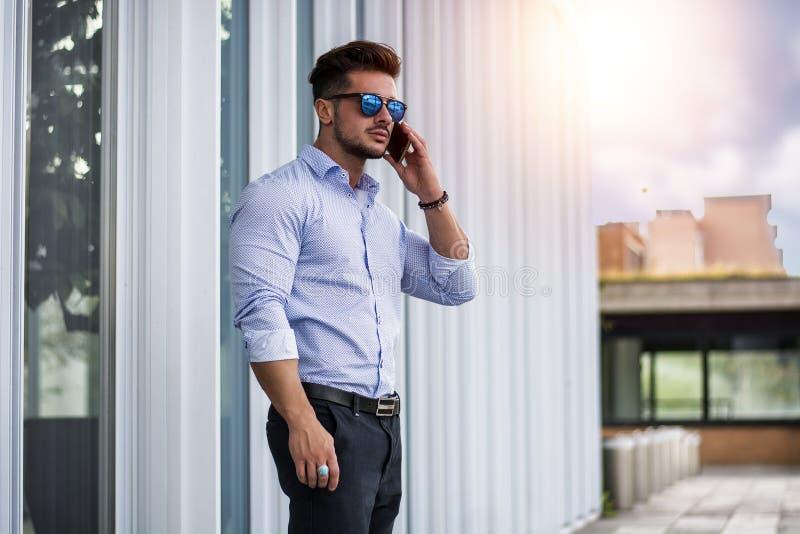 拜访手机外面在都市背景的帅哥 库存图片