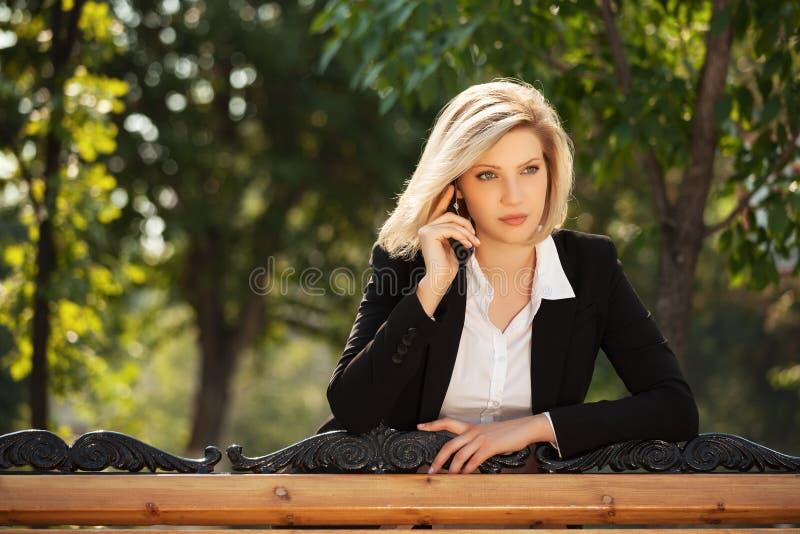 拜访手机的年轻女商人 库存照片