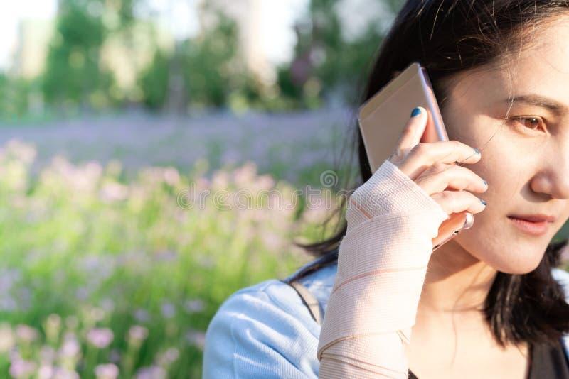 拜访智能手机的年轻学生妇女,当腕子手痛苦时 享用生活方式现代相当白人妇女的概念长沙发 库存照片