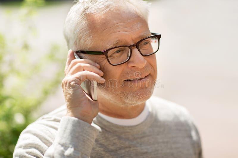 拜访智能手机的愉快的老人在城市 库存照片