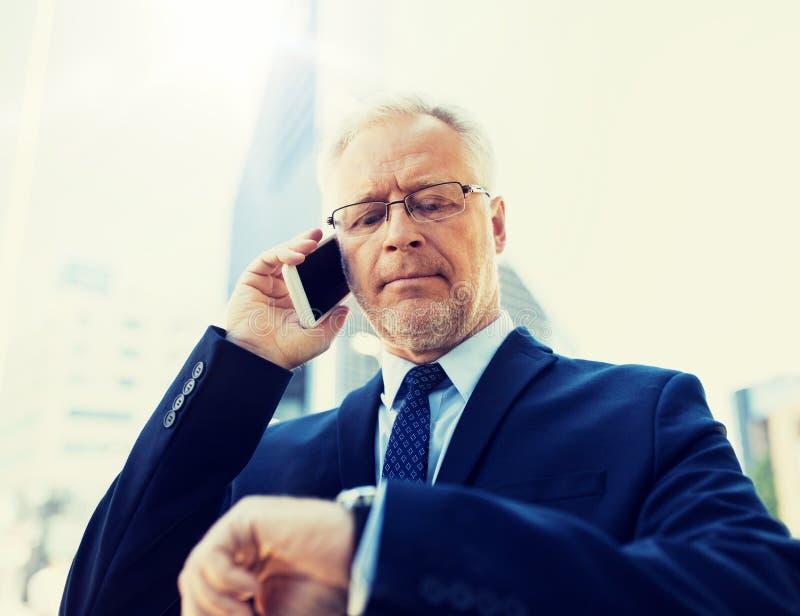 拜访智能手机的资深商人在城市 免版税图库摄影
