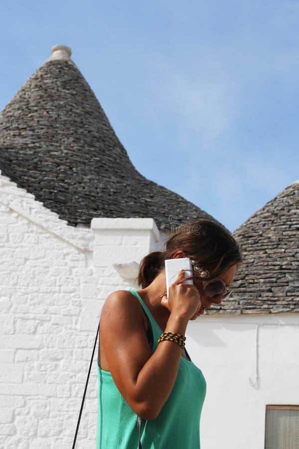 拜访电话的女孩 美女在阿尔贝罗贝洛村庄使用一个智能手机在Salento,意大利 库存图片