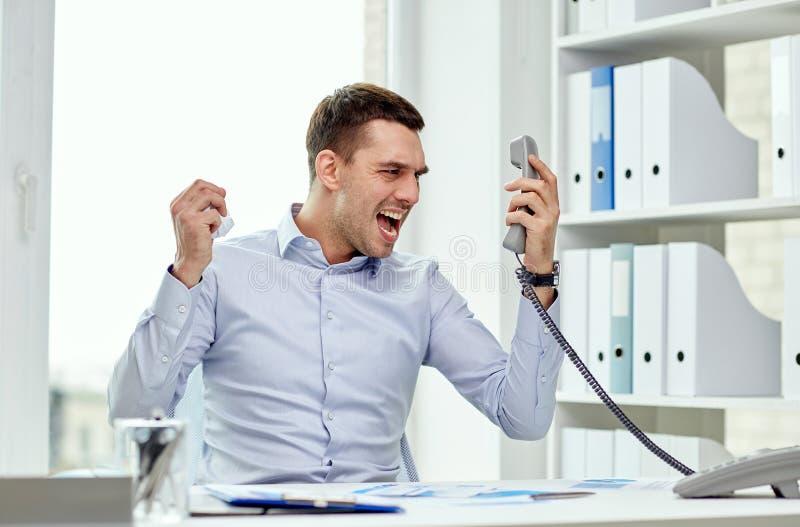拜访电话的愤怒的商人在办公室 库存照片