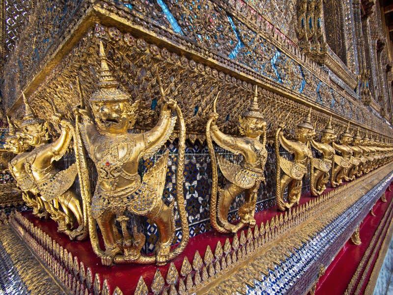 围拢鲜绿色菩萨的寺庙的监护人雕象 库存图片