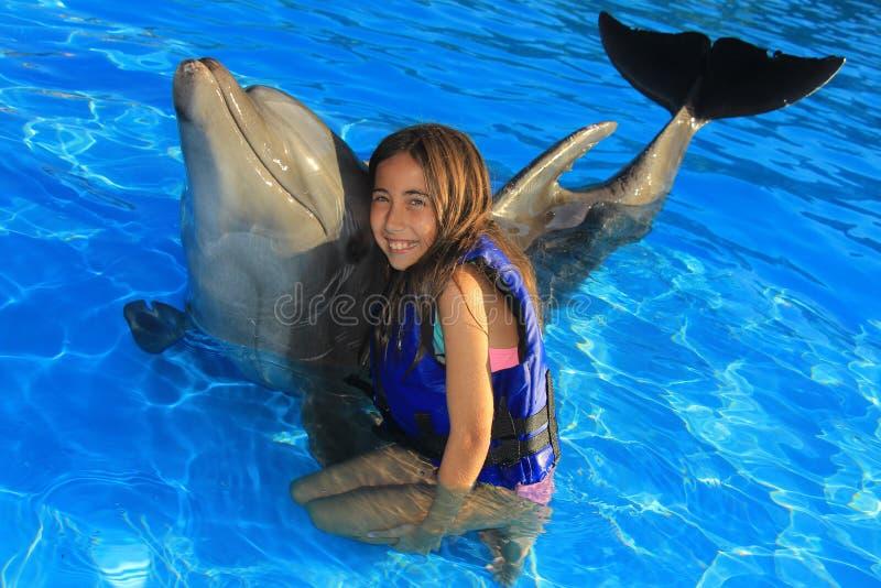 拥抱一个华美的海豚鸭脚板微笑的面孔愉快的孩子的小女孩孩子游泳瓶鼻子海豚 免版税图库摄影