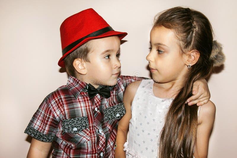 拥抱一个小女孩的典雅的男孩 免版税库存图片