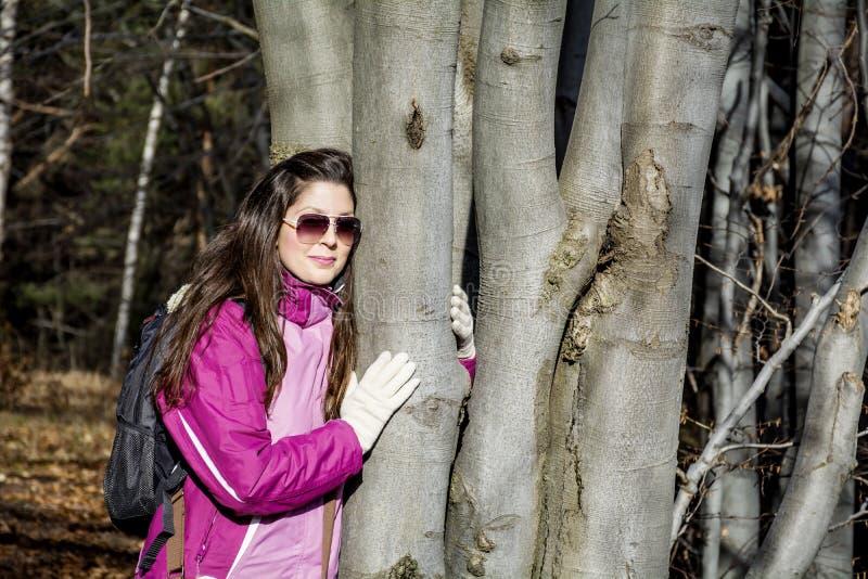 拥抱一个橡木词根的少妇在森林里 免版税库存图片