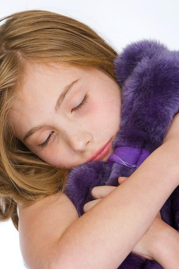 拥抱一个紫色玩具熊的逗人喜爱的女孩 免版税库存照片